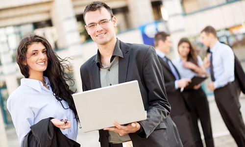 Young Businessman With A Laptop And Businesswoman Standing In Front Of Office Building Separated From The Rest Of The Business Team. With A Smile Looking At The Camera.
